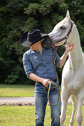 horse nuzzling a cowboy outdoors