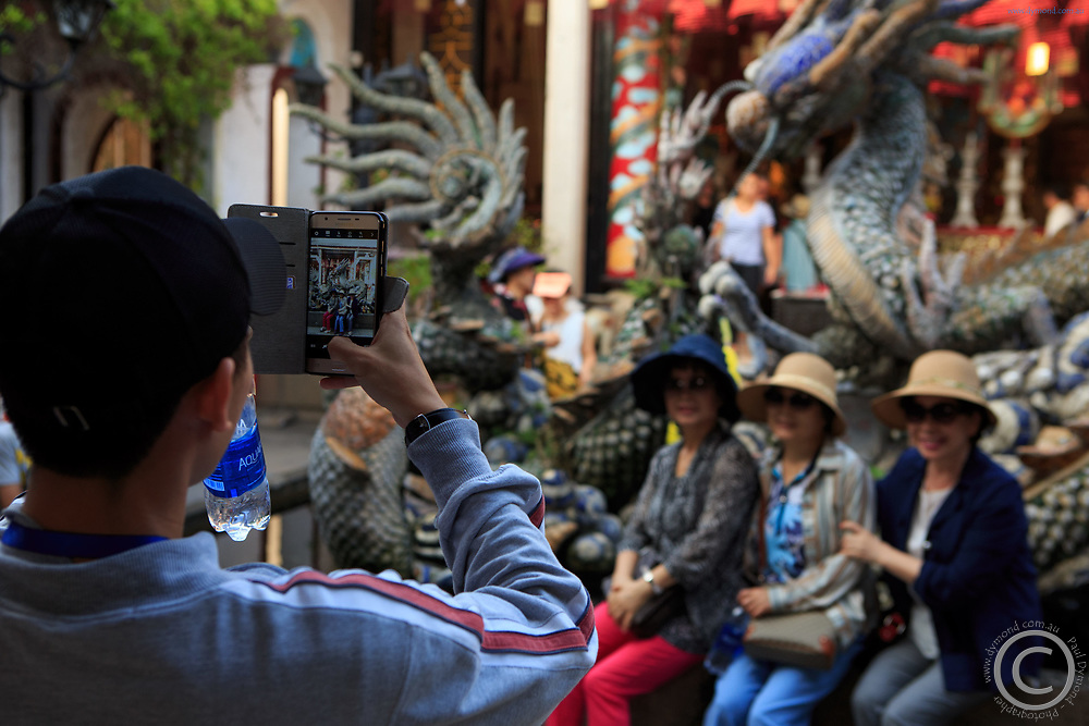 Tourists have their photo taken in the courtyard of the Cantonese Assembly Hall, Hoi An, Vietnam