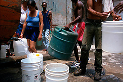Residents of central Havana line up at the neighborhood water truck with buckets to gather fresh water for their homes. (Photo © Jock Fistick)