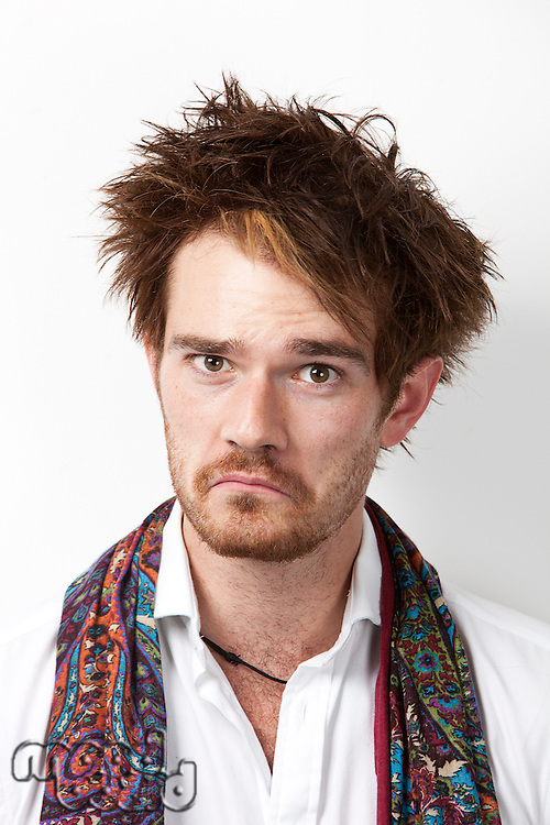 Portrait of young Caucasian man making a sad face against white background