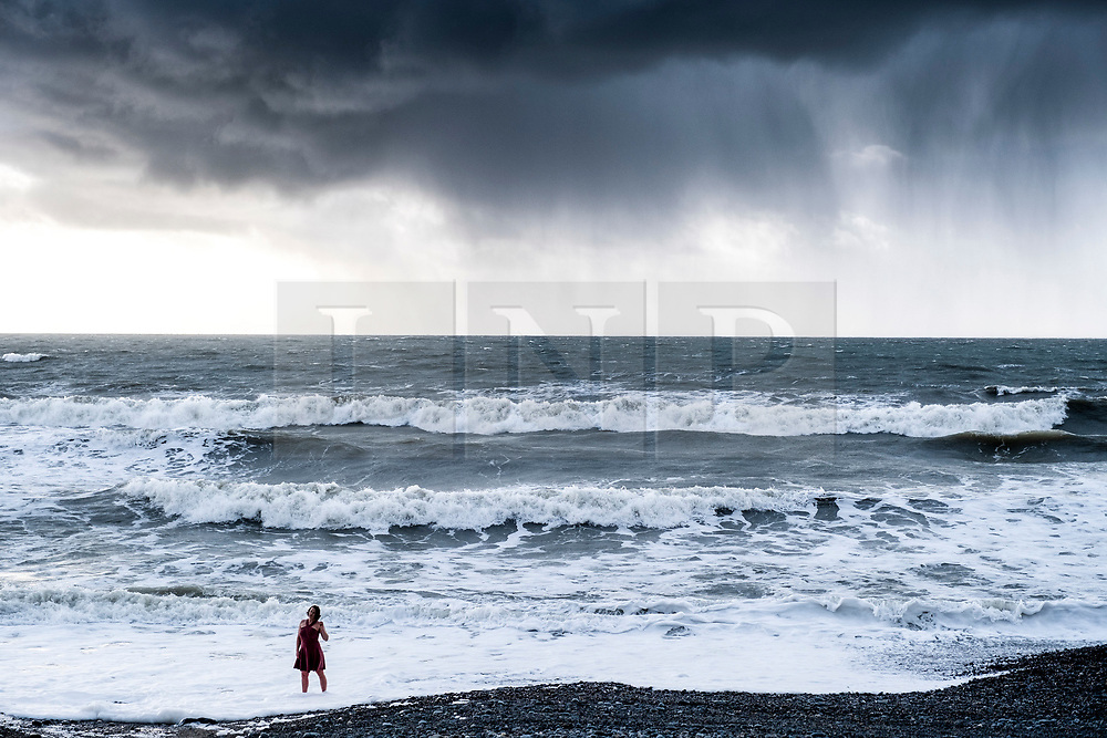 © Licensed to London News Pictures.04/03/2019.  Aberystwyth, UK. A woman poses for photos standing in the sea as behind her dramatic storm and rain clouds form over Cardigan Bay off the coast of Wales at Aberystwyth  on a blustery and cold day in the aftermath of Storm Freya. The weather for the week ahead is unsettled, with the threat of wintery snow and sleet showers. Photo credit: Keith Morris/LNP