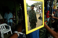 A member of the paramilitary group Bloque Norte, or Northern Block, is reflected in a mirror in La Mesa in northern Colombia on March 9, 2006. An estimated 24,000 paramilitary members have turned in their weapons as part of a government negotiated peace deal. But some are skeptical if the government plan will really work and if the paramilitary members will be successful in their transformation to civilian life. (Photo/Scott Dalton)