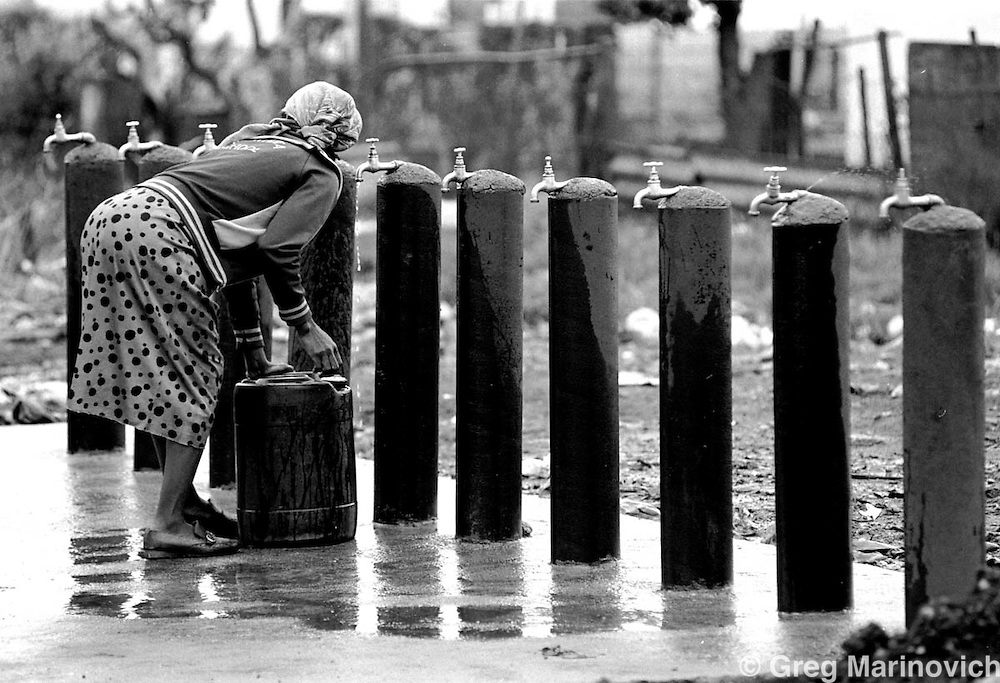 IPMG0475 South Africa, Kathlehong, 1992: A woman collects water from common standpipes in Mandela Park squatter camp in Kathlehong, Gauteng province, South Africa Oct 1992. Access to water is now a constitutional right. .Photograph by Greg Marinovich/South Photographs