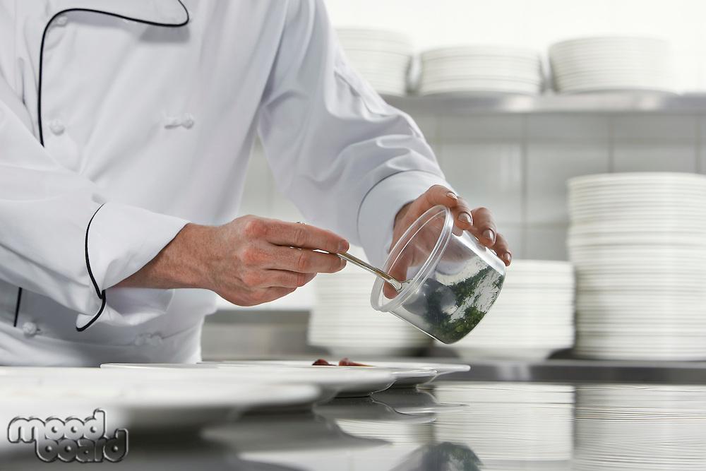 Chefs preparing salad in kitchen mid section