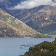 The TSS Earnslaw,  a 1912 Edwardian vintage twin screw steamer on the waters of Lake Wakatipu in, Queenstown, New Zealand. .It is one of the oldest tourist attractions in Central Otago, and the only remaining passenger-carrying coal-fired steamship in the southern hemisphere..The TSS Earnslaw heads along Lake Wakatipu from Queenstown  daily, running tourist trips to Walter Peak Station passing magnificent  peaks and contrasting shoreline foliage along the lakeside. Queenstown, New Zealand. 14th April 2011. Photo Tim Clayton