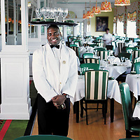 Jamaican Restaurant server readies the tables in photo by Architectural Lifestyle Photographer Wayne Cable, Grand Hotel. Mackinac Island Michigan for Coastal Living Magazine.<br />