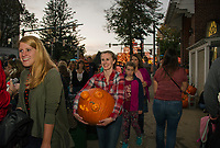 "Julie Pitman carries her ""Pumpkin Eater"" down Main Street to find a perfect viewing spot as the official count begins on Saturday evening for Pumpkin Fest in Laconia.  (Karen Bobotas/for the Laconia Daily Sun)"