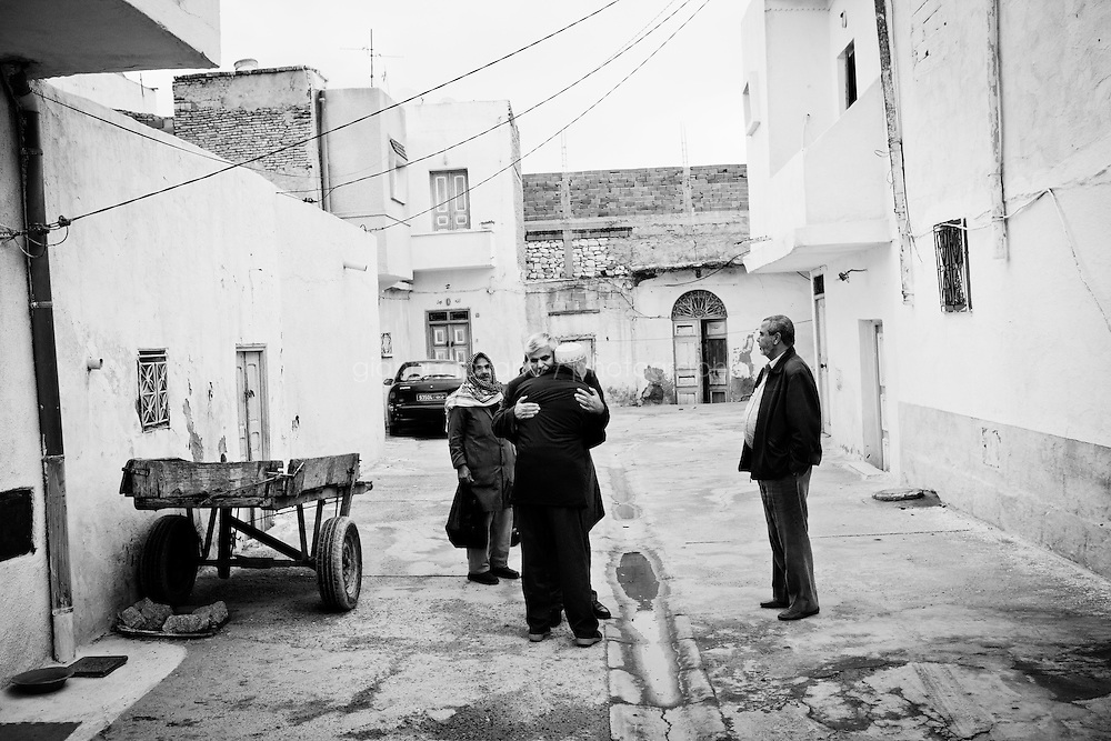 Kairouan, Tunisia - 18 December, 2011: Said Ferjani, 57, senior member of the political and communication bureau of the Nahda (Renaissance) party, hugs a friend he hasn't seen during his 22 years exile in front of his father's house who died in 2006 in Kairouan, Tunisia on 18 December, 2011. Said Ferjan's father died in Kairouan 2006 while Said was in exile in the UK since 1989. Said Ferjani started his activism in the Negra mosque of his hometown Kairouan when he was 16 years old, debating on politics, philosophy, economy and world events. In 1989 former dictator Zine El Abidine Ben Ali turned against Nahda (or Ennahda) and jailed 25,000 activists. Said Ferjani was jailed and tortured. He then flew Tunisia and moved to the UK. He came back to Tunisia after 22 years, after former dictator Ben Ali flew the country.<br /> <br /> Gianni Cipriano for The New York Times
