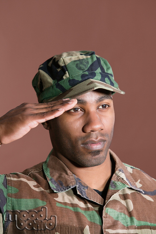 Close-up of a young African American US Marine Corps soldier saluting over brown background