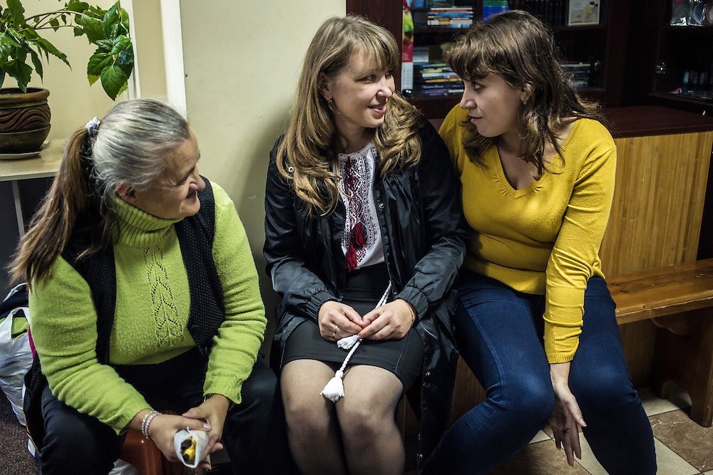 DNIPROPETROVSK, UKRAINE - OCTOBER 12: Lilia (R), who fled fighting in Ukraine's East with her husband, talks with other members of the congregation at Good News Evangelical Church on October 12, 2014 in Dnipropetrovsk, Ukraine. The United Nations has registered more than 360,000 people who have been forced to leave their homes due to fighting in the East, though the true number is believed to be much higher.(Photo by Brendan Hoffman/Getty Images) *** Local Caption ***