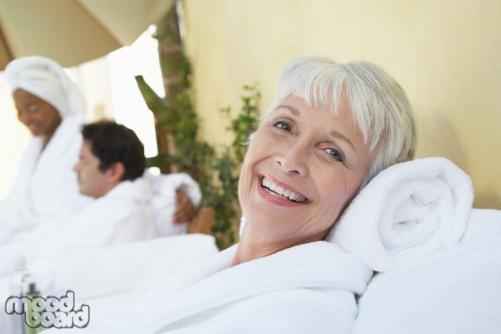 Woman relaxing at spa in bathrobe half length