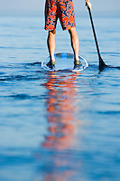 Close up of a man from waist down on a standup paddle board.