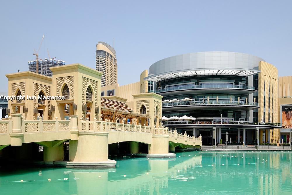 Exterior of Dubai Mall and ornate bridge crossing pond in Dubai United Arab Emirates