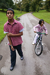 Brother and sister in park together with bicycle,