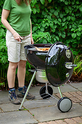 Using a Weber barbecue on a patio in summer