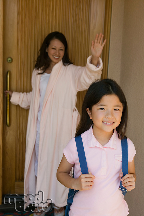 Mother Waving to Daughter as She Heads to School