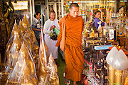 "05 JULY 2011 - BANGKOK, THAILAND:      A Buddhist monk and nun walk through shop selling Buddhist paraphernalia on Bamrung Muang Street in Bangkok. Thanon Bamrung Muang (Thanon is Thai for Road or Street) is Bangkok's ""Street of Many Buddhas."" Like many ancient cities, Bangkok was once a city of artisan's neighborhoods and Bamrung Muang Road, near Bangkok's present day city hall, was once the street where all the country's Buddha statues were made. Now they made in factories on the edge of Bangkok, but Bamrung Muang Road is still where the statues are sold. Once an elephant trail, it was one of the first streets paved in Bangkok, it is the largest center of Buddhist supplies in Thailand. Not just statues but also monk's robes, candles, alms bowls, and pre-configured alms baskets are for sale along both sides of the street.       PHOTO BY JACK KURTZ"