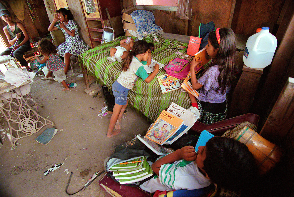Tamaulipas, Mexico, 1996 – Marisol and her siblings crowd into the main room of their home consisting of three small rooms constructed from particle board and aluminum sheets. From the right: Roibel, 11, Marisol, 8, Cristina, 6, Cynthia, 4 months, Nancy, 12, Eloisa, 3, and a neighbor.