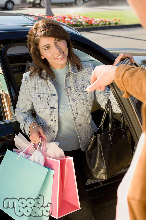 Woman with Shopping Bags Getting out of Car