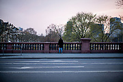 """Germany banned gatherings of more than 2 people called """"social distancing"""" because of the coronavirus. A man looking at the shore of river Main in Frankfurt which is very empty on a - normally very busy - Thursday evening."""