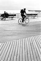 A man rides his bicycle on the boardwalk, Brooklyn, New York, NY