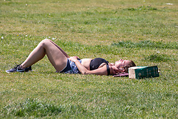 © Licensed to London News Pictures. 07/05/2020. London, UK. A sunbather enjoys the hazy sunshine on Richmond Green in South West London were temperatures are predicted to reach 25c for the Bank Holiday VE Day celebrations as Prime Minister Boris Johnson is expected to announce a relaxation of lockdown rules in his address to the Nation on Sunday. Photo credit: Alex Lentati/LNP