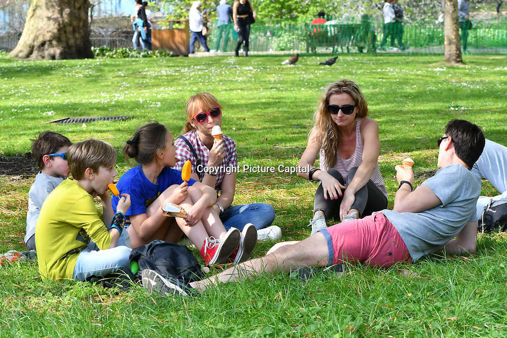Tourists sunbath,feeding birds, and eating ice-cream at the Royal park London on 22 April 2019.