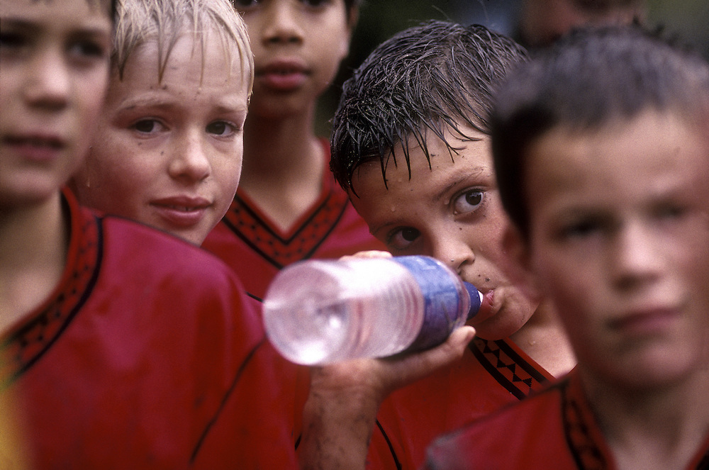 USA, Washington, Seattle, Boys on McGilvra Soccer Club Geckos team stand soaked during muddy game at Arboretum