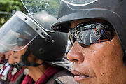 07 AUGUST 2013 - BANGKOK, THAILAND: An empty street reflected in the sunglasses of a Thai riot policeman on Ratchawithi road in Bangkok. About 2,500 protestors opposed to an amnesty bill proposed by Thailand's ruling party marched towards the Thai parliament in the morning. The amnesty could allow exiled fugitive former Prime Minister Thaksin Shinawatra to return to Thailand. Thaksin's supporters are in favor of the bill but Thai Yellow Shirts and government opponents are against the bill. Thai police deployed about more than 10,000 riot police and closed roads around the parliament. Although protest leaders called off the protest rather than confront police, a few people were arrested for assaulting police when they tried to break through police lines. Several police officers left the scene under medical care after they collapsed in the heat.    PHOTO BY JACK KURTZ