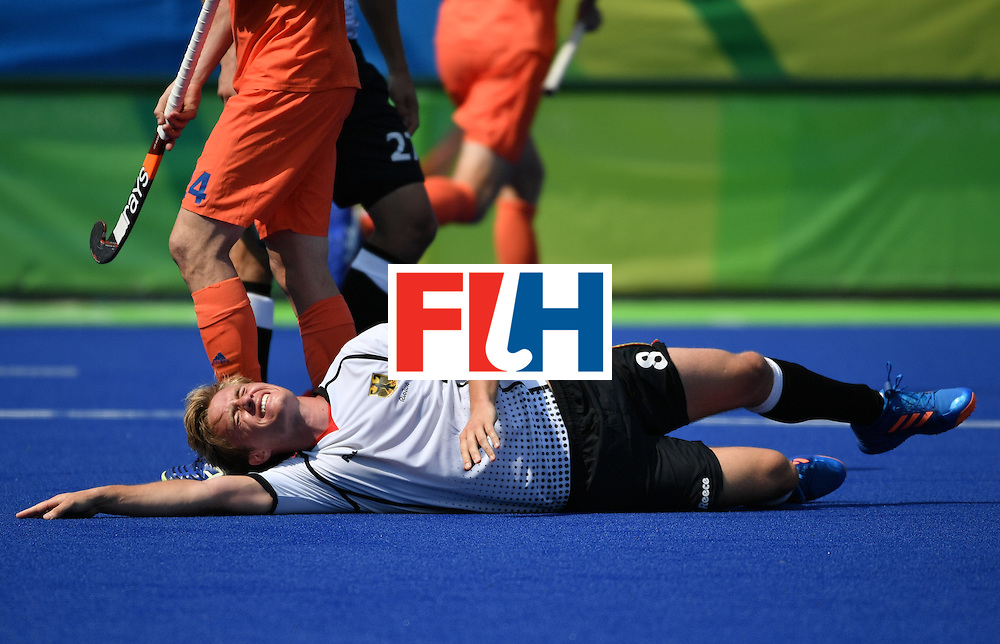 Germany's Mats Grambusch lies on the pitch after getting injured during the men's Bronze medal field hockey Netherlands vs Germany match of the Rio 2016 Olympics Games at the Olympic Hockey Centre in Rio de Janeiro on August 18, 2016. / AFP / Pascal GUYOT        (Photo credit should read PASCAL GUYOT/AFP/Getty Images)