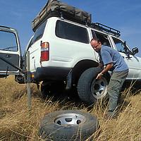 Africa, Kenya, Masai Mara Game Reserve, (MR) Photographer Paul Souders changes tire of Toyota Land Cruiser on safari