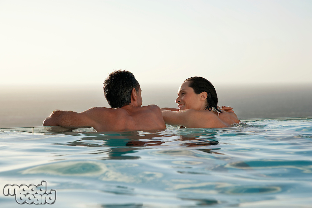 Couple relaxing in infinity pool at sunset back view