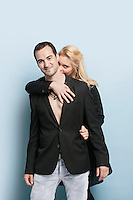 Portrait of young woman embracing man from behind against light blue background