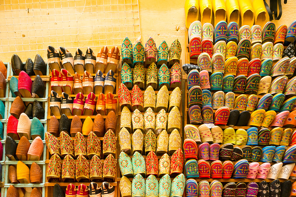 FEZ, MOROCCO 2ND FEBRUARY 2018 - Colourful babouches and tailor made Moroccan shoes and slippers hang for sale on a wall in the old Fez Medina, Middle Atlas Mountains, Morocco.