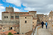 Tourists strolling along the top of the medieval city wall in Avila, Spain