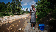 A woman stands on the banks of a Cholera contaminated stream; the only source of water in Dofine, Haiti, Tuesday, November 7, 2017. Photo: Bryan Woolston / @woolstonphoto
