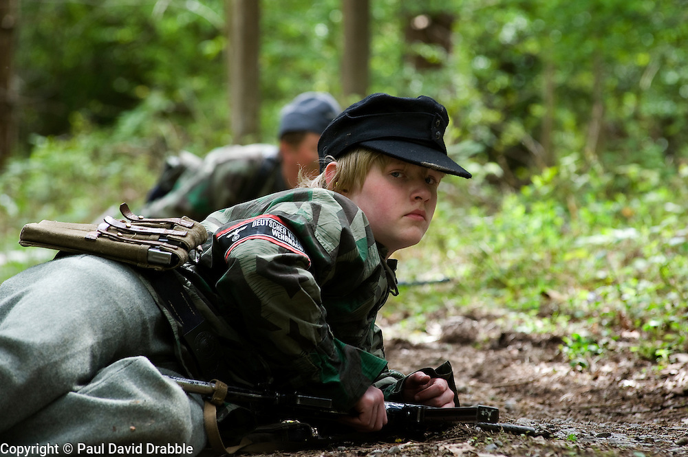 A young Reenactor from Northern World War Two Association, dressed as a member of the Volkssturm or peoples army pinned down by allied fire on a dirt road during a private 24hr excerise, held at Sutton Grange, near Ripon in Yorkshire 15  May 2010 .Images © Paul David Drabble.