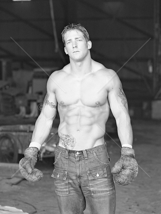 shirtless tattooed boxer standing in a warehouse