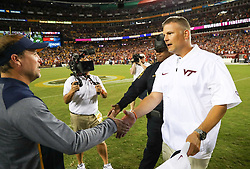Sep 3, 2017; Landover, MD, USA; Virginia Tech Hokies head coach Justin Fuente and West Virginia Mountaineers head coach Dana Holgorsen speak at midfield at the end of the game at FedEx Field. Mandatory Credit: Ben Queen-USA TODAY Sports