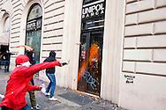 """Roma, 27 Ottobre 2012: .No Monti Day, manifestazione nazionale contro le politiche del  governo Monti..Un gruppo di manifestanti lancia la vernice contro una banca in via Cavour..""""No Monti Day"""" protest in Rome against the austerity cuts of the Italian government.."""