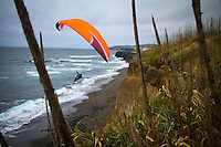 Paraglider Gavin McClurg soars along cliffs on the north side of Sao Miguel in the Azores