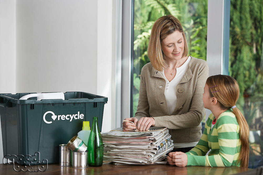 Woman and girl preparing waste paper for recycling