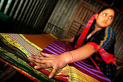 BANGLADESH SIRAJGANJ RADHUNIBARI 30JAN07 - A Bangladeshi woman irons finished saris prior to packaging and dispatch in a rural weaving community. Records of an indigenous weaving industry based on handlooms producing cotton fabrics date back to the 13th century in this area.<br /><br /> <br /> jre/Photo by Jiri Rezac<br /> <br /> <br />© Jiri Rezac 2007