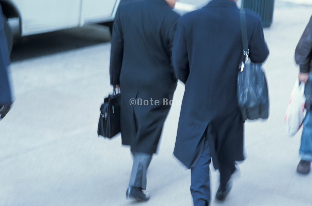 tinted view of 2 businessmen walking in city