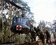 Assault on Hill 875, Vietnam, November 1967:  Members of 173d Airborne Brigade load casualties onto a helicopter carrying the emblem of the Red Cross for evacuation to a field hospital.