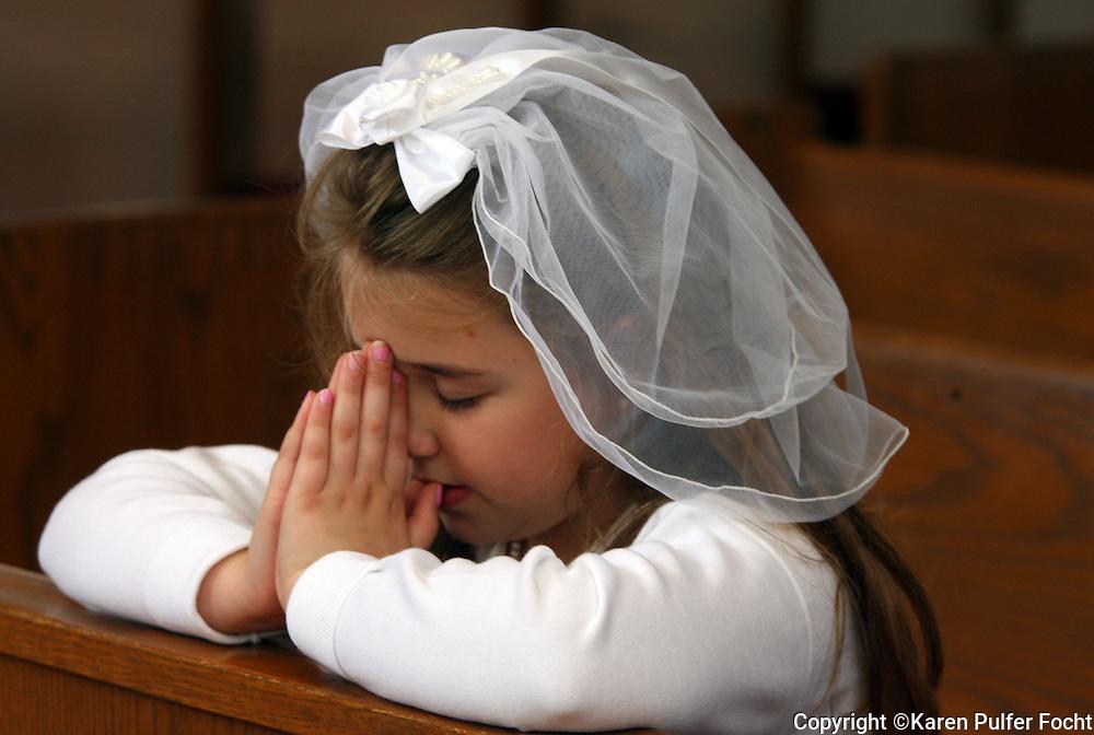 Elizabeth Focht prays following her first communion.