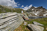 Two female hikers are resting on a rock close to the lake Geisspfadsee, Landschaftspark Binntal, Valais, Switzerland