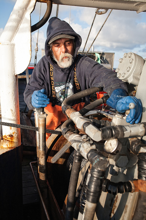 Brad Burton begins the task of pulling the bags up from below using the winch. A winch is located on both sides of the trawler and there must be someone operating each winch at the same time.