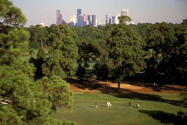 Golfers enjoying a sunny Houston day at Memorial Park with the downtown skyline in the background.