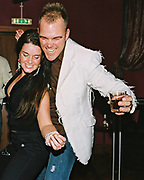 A man and woman dance whilst holding a drink at Funktup, December 2004